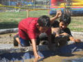 092216_LOSNIETOS_MUDRUN1: Ada S. Nelson Elementary students crawl their way through a pit of mud on Sept. 16 for the school's second annual Mud Run, which raised $6,600 for the Parent Teacher Organization.